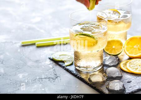 Homemade citrus lemonade in glasses with ice on slate. - Stock Photo