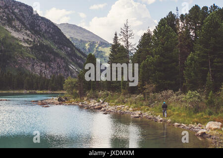 Lake with rocky ridge. Beautiful landscape. The tourist goes over the rocks on the shore of the lake. Altay Russia. - Stock Photo