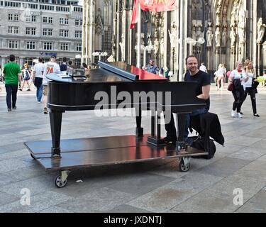 Man playing on grand piano in pedestrian zone in front of Cologne Cathedral main entrance - Stock Photo