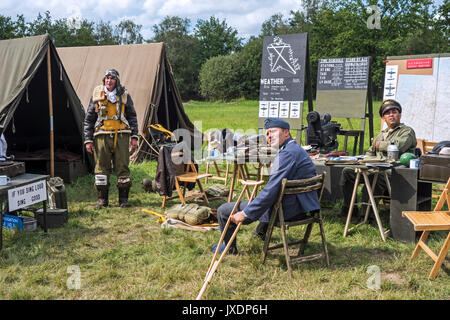 Re-enactors in World War Two battle dresses posing in military re-enactment field camp at WW2 militaria fair - Stock Photo
