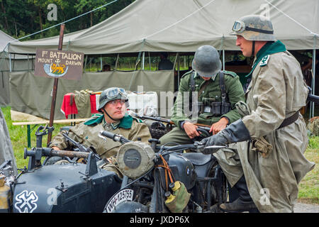 Re-enactors in German WW2 soldier outfits on BMW military motorcycle with sidecar during World War Two re-enactment - Stock Photo