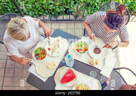 Modern mom and young daughter eating lunch sitting at the table in a water park on summertime. Concept of beautiful - Stock Photo