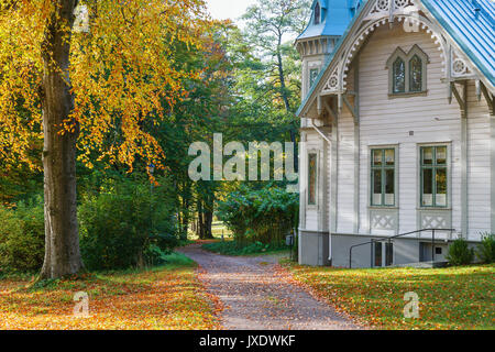 Old wooden house with a footpath in the garden - Stock Photo