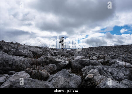 Mountain walker in silhouette against cloudy sky on rock field leading up to top cairn of a Munro in the Scottish - Stock Photo