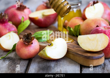Apples, pomegranate and honey - symbols of judaic holiday Rosh Hashana (Jewish New Year). Selective focus. - Stock Photo