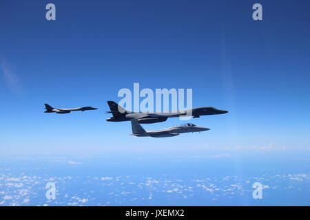 Two U.S. Air Force B-1B Lancer bombers with the 37th Expeditionary Bomb Squadron is escorted by a Japan Air Self - Stock Photo
