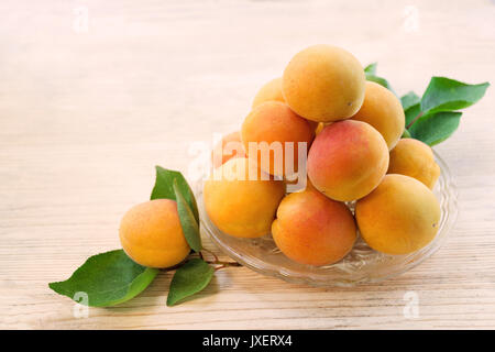 Fresh apricot. Ripe apricots with leaves on a glass plate. Wooden background. Top view. Copy space - Stock Photo
