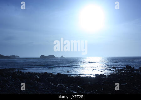 British Channel Islands. Alderney. View of coast and distant Fort Clonque in bright early evening sun. - Stock Photo