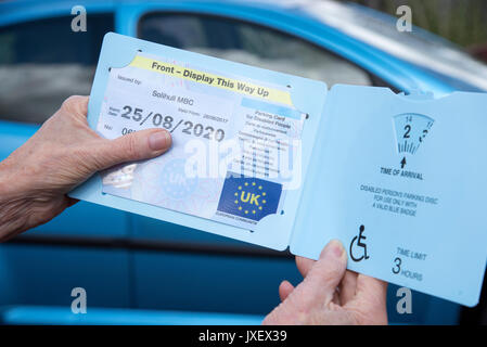 Woman's hands holding a Blue Badge parking disc issued in the UK to disabled drivers - Stock Photo