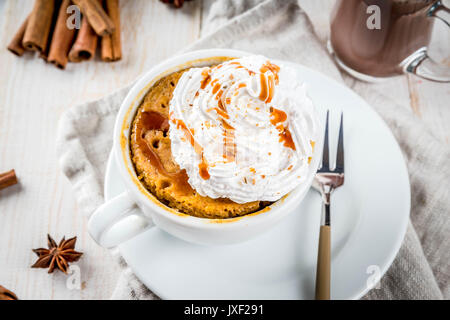 Recipes with pumpkins, fast food, microwave meal. Spicy pumpkin pie in mug, with whipped cream, ice cream, cinnamon, - Stock Photo