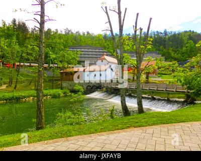 View on waterfall, mill in white building, pedestrian bridge in Park Postojna jama near Postojna Cave - Stock Photo