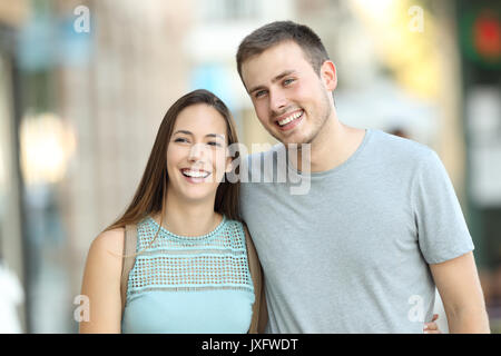 Front view portrait of a happy couple walking together on the street - Stock Photo
