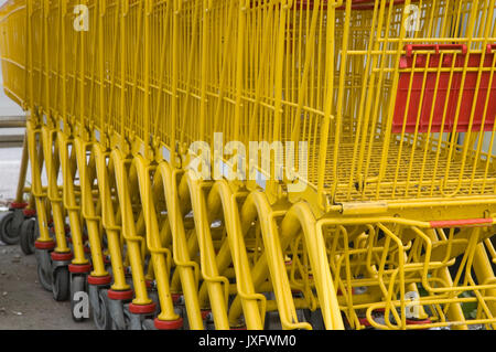 yellow shopping carts parked in row - Stock Photo