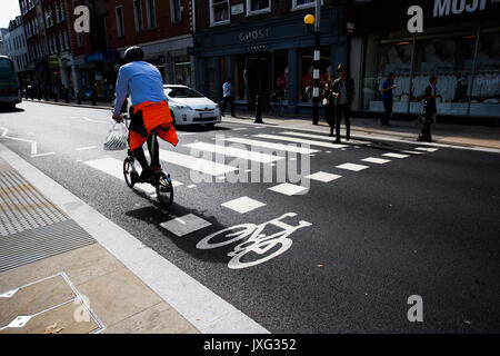 A London worker cycling over zebra crossing whilst car waits for pedestrian on Kings Road, Sloane Square, London. - Stock Photo