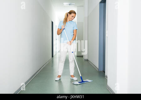 Happy Female Janitor Cleaning The Floor With Mop On The Corridor Of The Building - Stock Photo