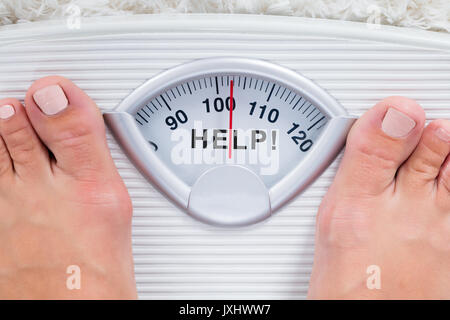 Close-up Of Overweight Person Feet On Weight Scale Indicating Help - Stock Photo