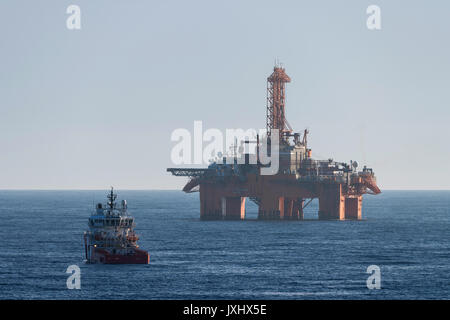 Supply vessel in front of West Phoenix oil rig, oil extraction, North Sea - Stock Photo
