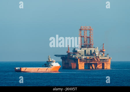 Supply vessel Normand Aurora next to West Phoenix oil rig, oil extraction, North Sea - Stock Photo
