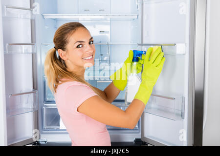 Young Happy Cleaning Lady Cleaning The Empty Refrigerator Door With Spray Bottle And Sponge - Stock Photo