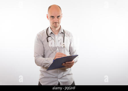 Man with white shirt and medical stethoscope holding and writing something on clip board over white background - Stock Photo