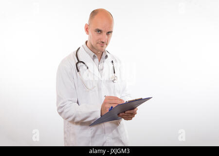 Man with white coat and stethoscope looking at camera while holding and writing something on clip board over white - Stock Photo