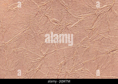 Light brown wavy background from a textile material. Fabric with fold texture closeup. Creased shiny beige cloth. - Stock Photo
