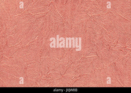 Light red wavy background from a textile material. Fabric with fold texture closeup. Creased shiny coral cloth. - Stock Photo