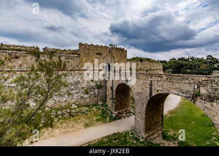 Gate of Saint John and bridge leading to it over moat, Rhodes old town, Greece - Stock Photo
