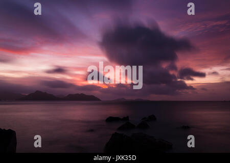 Colorful sunset view to Praslin from La Digue, Seychelles. Long exposure shot. - Stock Photo