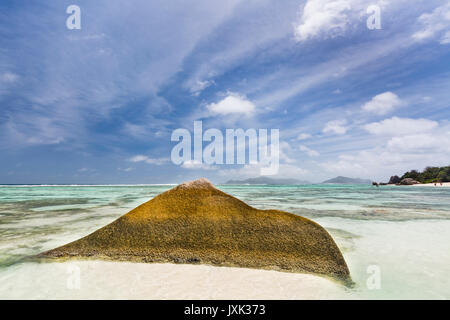 A beautiful scenic granite rock at Anse Source D'Argent in La Digue, Seychelles with clear lagoon and blue sky - Stock Photo