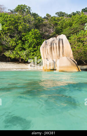 Beach and granie rocks in La Digue, Seychelles seen from the water in the evening - Stock Photo