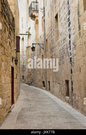 A narrow street in the walled city of Mdina Malta lined by old stone buildings -the silent city - Stock Photo
