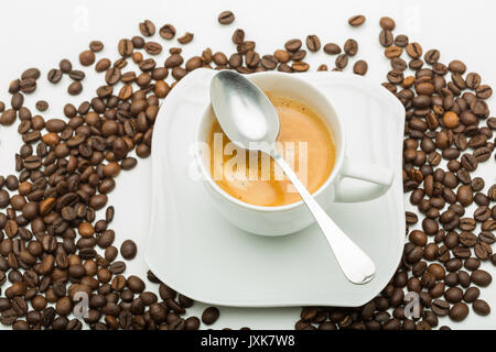 A white cup of coffee and a white saucer seen from the top with coffee beans. - Stock Photo