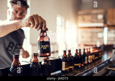 Young man examining the quality of beer. Beer bottles moving on conveyor belt in brewery factory with brewer testing - Stock Photo