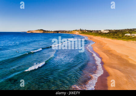 Aerial elevated photo along waterline on Mona Vale Narrabeen beach with surfers, clean sand and blue waves. - Stock Photo