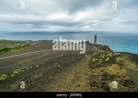 Capelinhos volcanic area on the coast of Faial island, with the Lighthouse of Ponta dos Capelinhos in the background - Stock Photo