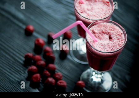 Fresh cool smoothie in a glass with a stem. Delicious and healthy Breakfast.Of cherries and strawberries - Stock Photo
