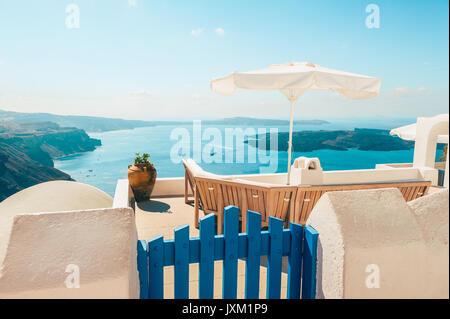 Bench on terrace overlooking Caldera of Santorini Greece - Stock Photo