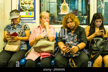 Senior woman surrounded by other passengers on mobile phones on the MRT (Mass Rapid Transport) sytem), Bangkok, - Stock Photo