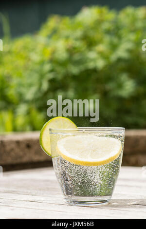 Glass of gin and tonic or vodka and tonic or fizzy water on a wooden table. Refreshing - Stock Photo