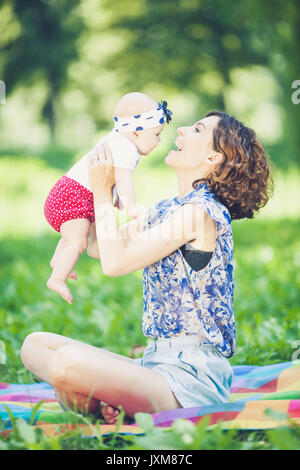 Young beautiful mother sits on blanket with her daughter during a picnic in the park - Stock Photo