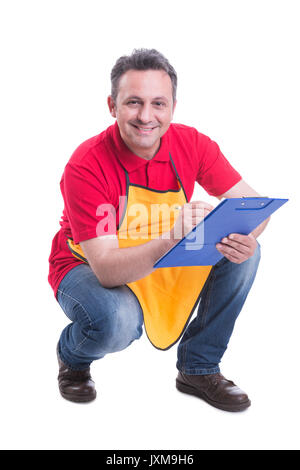 Smiling salesman counting products on supermarket shelf and taking notes on clipboard - Stock Photo