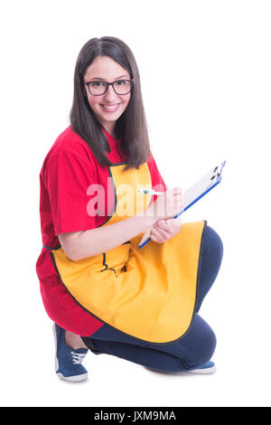 Smiling young supermarket seller counting the products on white background - Stock Photo
