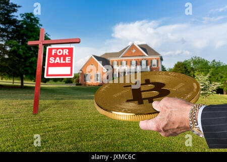 Businessman hand offering Bitcoin to buy house - Stock Photo