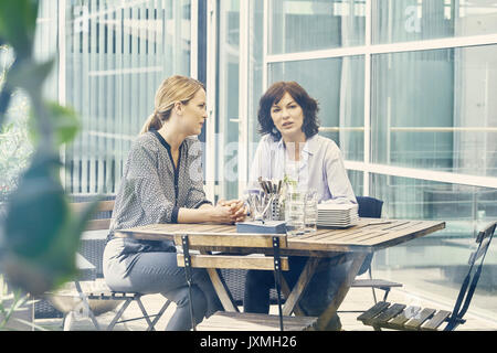 Two businesswomen having discussion during business lunch outside office - Stock Photo