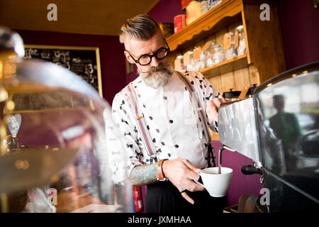 Quirky vintage senior man preparing coffee behind cafe counter - Stock Photo