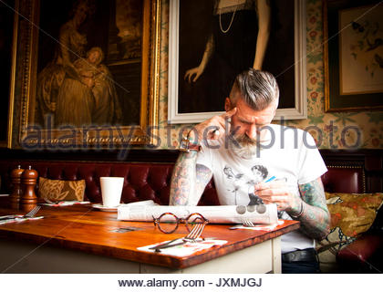 Quirky man doing crossword in bar and restaurant, Bournemouth, England - Stock Photo