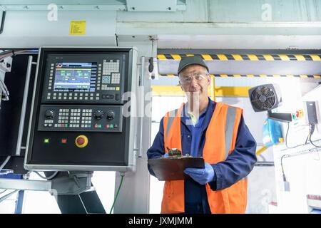 Portrait of engineer with locomotive wheel lathe in train works