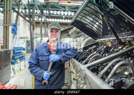 Portrait of apprentice engineer with locomotive engine in train works