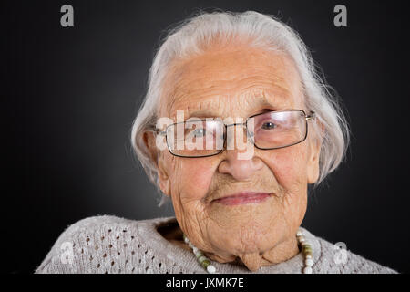 Portrait Of Smiling Senior Woman With Eyeglasses Over Grey Background - Stock Photo